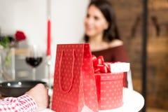 在家庆祝华伦泰与晚餐的年轻愉快的夫妇` s天 图库摄影
