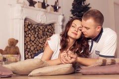 在家庆祝圣诞节和新年的爱恋的夫妇坐 库存照片