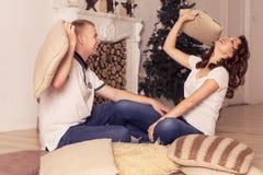 在家庆祝圣诞节和新年的爱恋的夫妇坐 免版税图库摄影