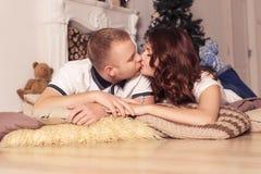 在家庆祝圣诞节和新年的爱恋的夫妇坐 免版税库存图片