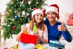 在家庆祝圣诞节的年轻夫妇 免版税库存照片