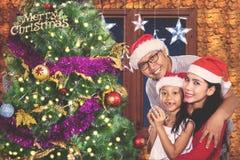 在家庆祝圣诞节的年轻家庭 免版税库存图片