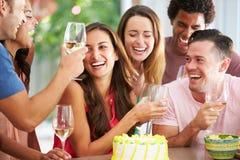在家庆祝生日的小组朋友 免版税库存图片