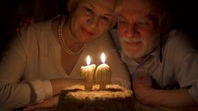 在家庆祝70s与蛋糕的爱恋的资深夫妇周年在晚上 吹的蜡烛 股票录像
