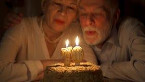 在家庆祝70s与蛋糕的爱恋的资深夫妇周年在晚上 吹的蜡烛 股票视频