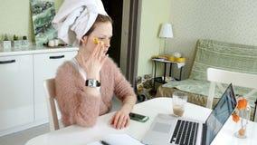 在家应用化妆面部斑点的可爱的女商人,工作在膝上型计算机后 股票录像