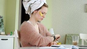 在家应用化妆面部斑点的可爱的女商人,工作在膝上型计算机后 影视素材