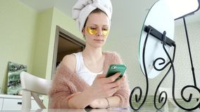 在家应用化妆面部斑点的可爱的女商人,谈话在电话 股票录像