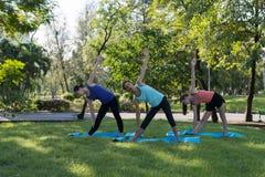 在家庭、母亲和女儿的活动放松的瑜伽席子的 免版税库存照片
