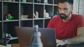 在家庭办公室刮胡须人运转的便携式计算机 看膝上型计算机屏幕的人 股票录像