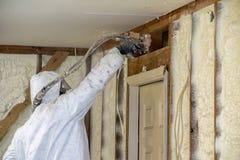 在家庭墙壁上的工作者喷洒的闭合的细胞浪花泡沫绝缘材料 免版税库存照片