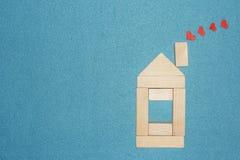 在家庭概念的爱 木房子和红色心脏从烟囱在蓝色背景用管道输送 库存图片
