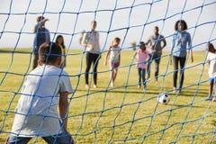 在家庭橄榄球赛期间的男孩保卫的目标 免版税图库摄影