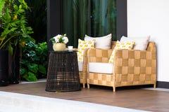 在家庭菜园的一个现代柳条沙发,庭院看法  免版税库存图片