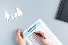 在家庭观念的收养形式在灰色背景顶视图大模型 免版税库存照片