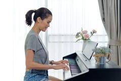 在家弹电子钢琴的亚裔美女 看见从侧视图,当按钢琴键的她由两只手时 ? 免版税库存图片