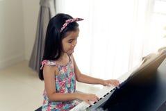 在家弹电子钢琴的年轻矮小的亚裔逗人喜爱的女孩 免版税图库摄影