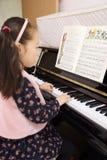 在家弹钢琴的小女孩 免版税图库摄影