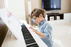 在家弹钢琴的小孩男孩 免版税库存照片