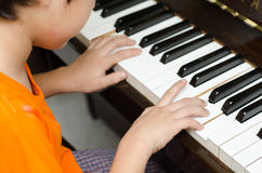 在家弹钢琴的小男孩 免版税库存照片