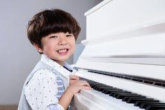 在家弹钢琴的愉快的亚裔中国小男孩 免版税库存图片