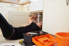 在家当学徒修理厨房水槽的水管工 免版税库存图片