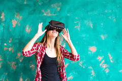 在家得到经验使用虚拟现实VR耳机玻璃姿势示意的手的微笑愉快的妇女 库存照片