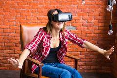 在家得到经验使用虚拟现实VR耳机玻璃姿势示意的手的微笑愉快的妇女 图库摄影