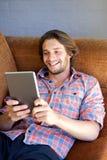在家微笑与数字式片剂的年轻人 库存照片