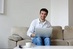 在家微笑与膝上型计算机的年轻人 免版税库存图片