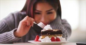 在家微笑与蛋糕的愉快的亚裔妇女 免版税图库摄影