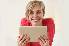 在家微笑使用数字式片剂垫客厅长沙发的年轻美丽的愉快的30s妇女 库存图片
