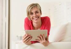 在家微笑使用数字式片剂垫客厅长沙发的年轻美丽的愉快的30s妇女 免版税库存照片