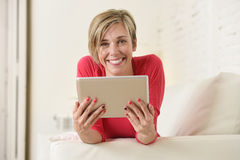 在家微笑使用数字式片剂垫客厅长沙发的年轻美丽的愉快的30s妇女 库存照片