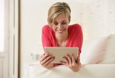 在家微笑使用数字式片剂垫客厅长沙发的年轻美丽的愉快的30s妇女 图库摄影