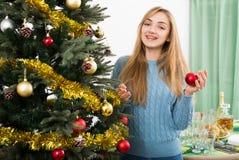 在家微笑的少妇装饰Xmas树和 免版税库存图片