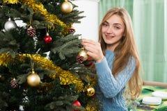 在家微笑的少妇装饰Xmas树和 免版税库存照片