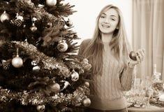 在家微笑的少妇装饰Xmas树和 库存照片
