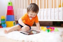 在家微笑18个月有片剂计算机的婴孩 免版税库存照片