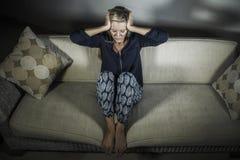 在家感觉被挫败的开会沙发长沙发s的40s沮丧的和急切美丽的白肤金发的妇女遭受的消沉和头疼 免版税库存照片
