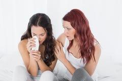 在家慰问一个哭泣的女性朋友的妇女 免版税图库摄影