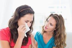 在家慰问一个哭泣的女性朋友的妇女 库存图片