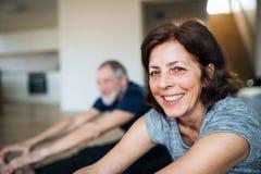 在家户内一对资深夫妇,做在地板上的锻炼 库存图片