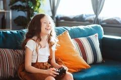 在家打与gamepad的愉快的孩子电子游戏 免版税图库摄影