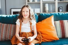 在家打与gamepad的愉快的孩子电子游戏 库存照片
