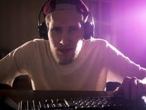 在家打在一台计算机上的年轻有胡子的人接近的画象电子游戏在夜 库存图片
