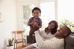 在家打在沙发的父母和儿子比赛 图库摄影