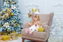 在家打开一件礼物的小女孩在客厅 免版税图库摄影