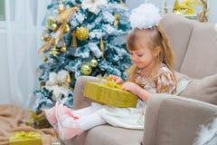 在家打开一件礼物的小女孩在客厅 免版税库存照片