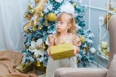 在家打开一件礼物的小女孩在客厅 图库摄影